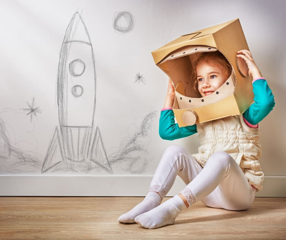 child playing make believe and using art to build a space ship out of cardboard