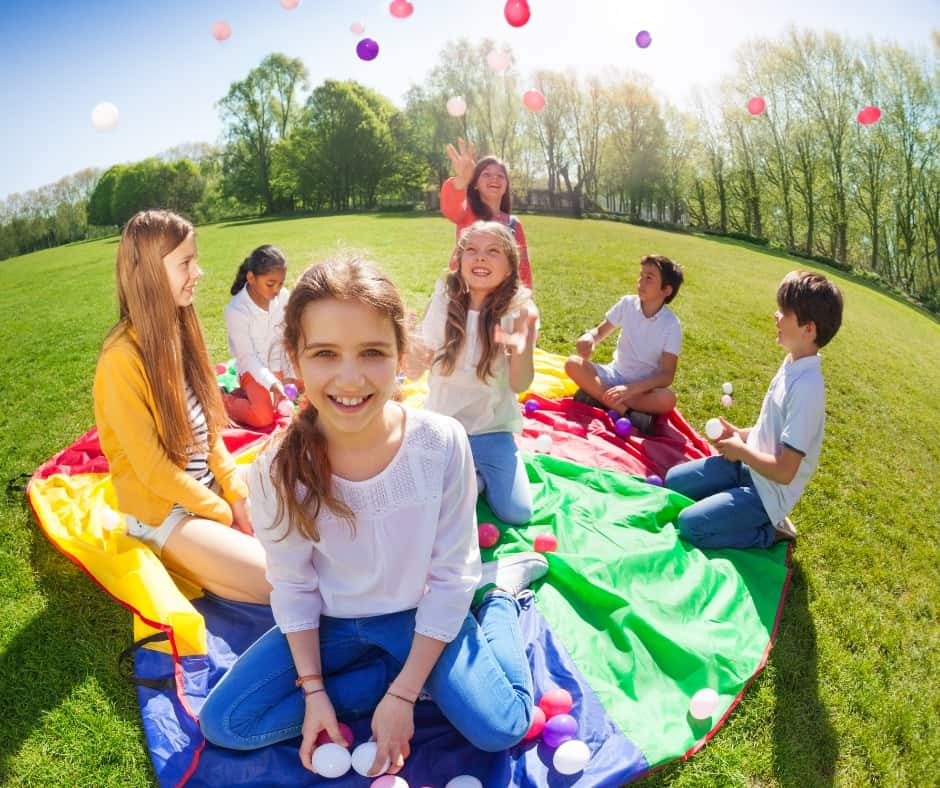 kids enjoying a kite and balloons in a field in the summer