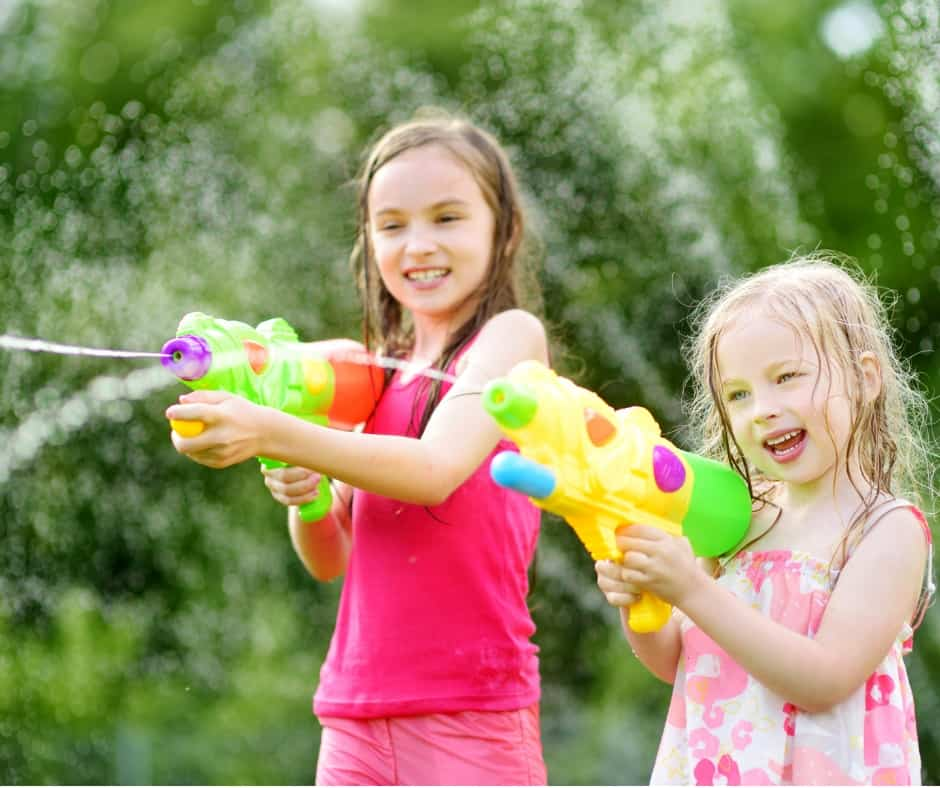 two girls have a water fight with family