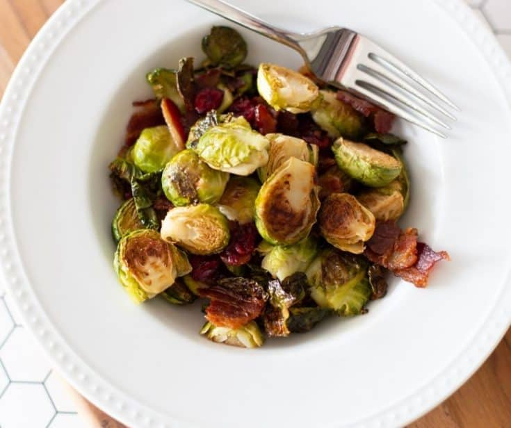 roasted Brussel sprouts with bacon and cranberries in a white bowl with fork on the side by The Moments At Home