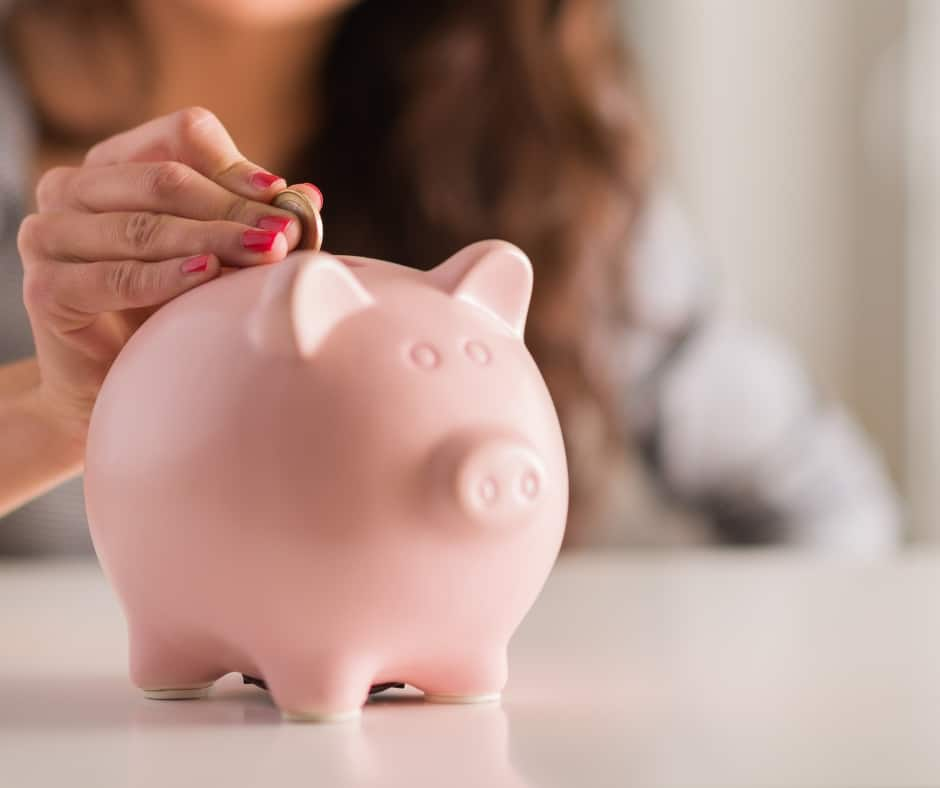 frugal woman putting money into piggy bank to save money