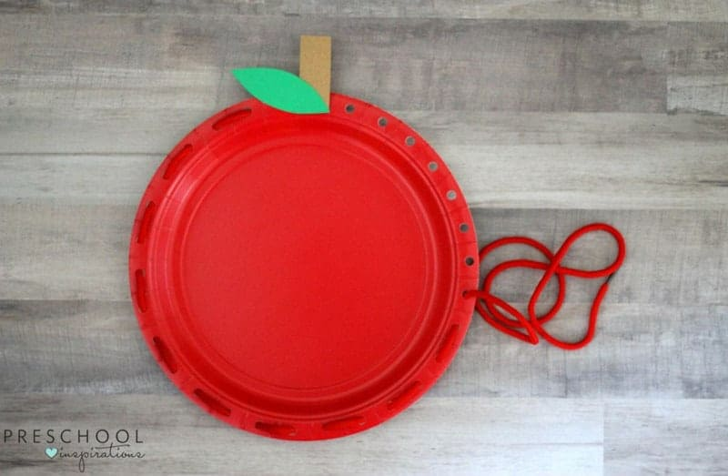 painted paper plate craft in the shape of an apple with lacing for fine motor skill development finished example