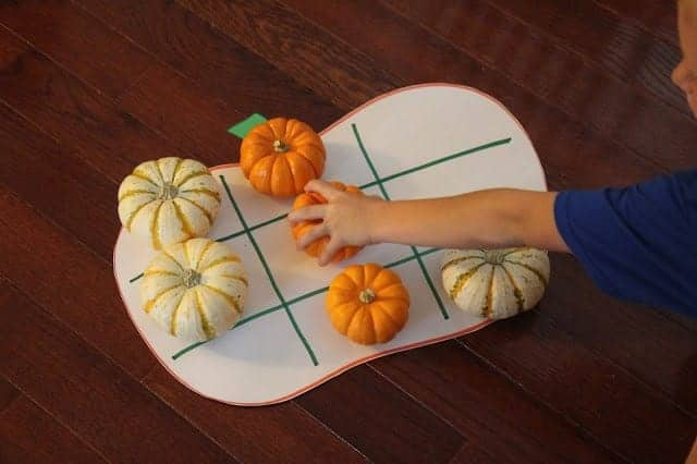 toddler hands playing tic tac toe on a giant cut out pumpkin with multi colored gourds instead of X's and O's