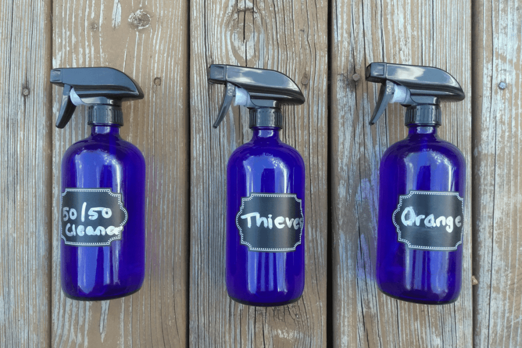 "3 blue glass bottles holding homemade non-toxic cleaning solutions with spray tops and labels saying ""50/50, thieves, and orange"""