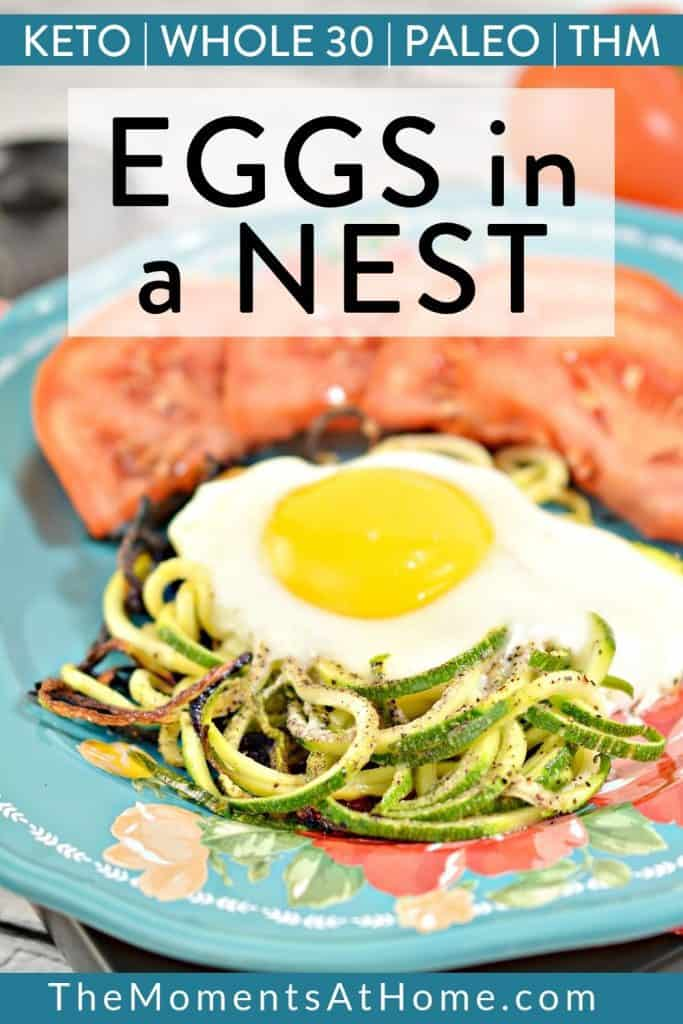 "sunny side up egg on zoodles on a blue plate with tomato wedges with text ""keto, paleo, whole 30, THM zucchini eggs in a nest"" by the moments at home"