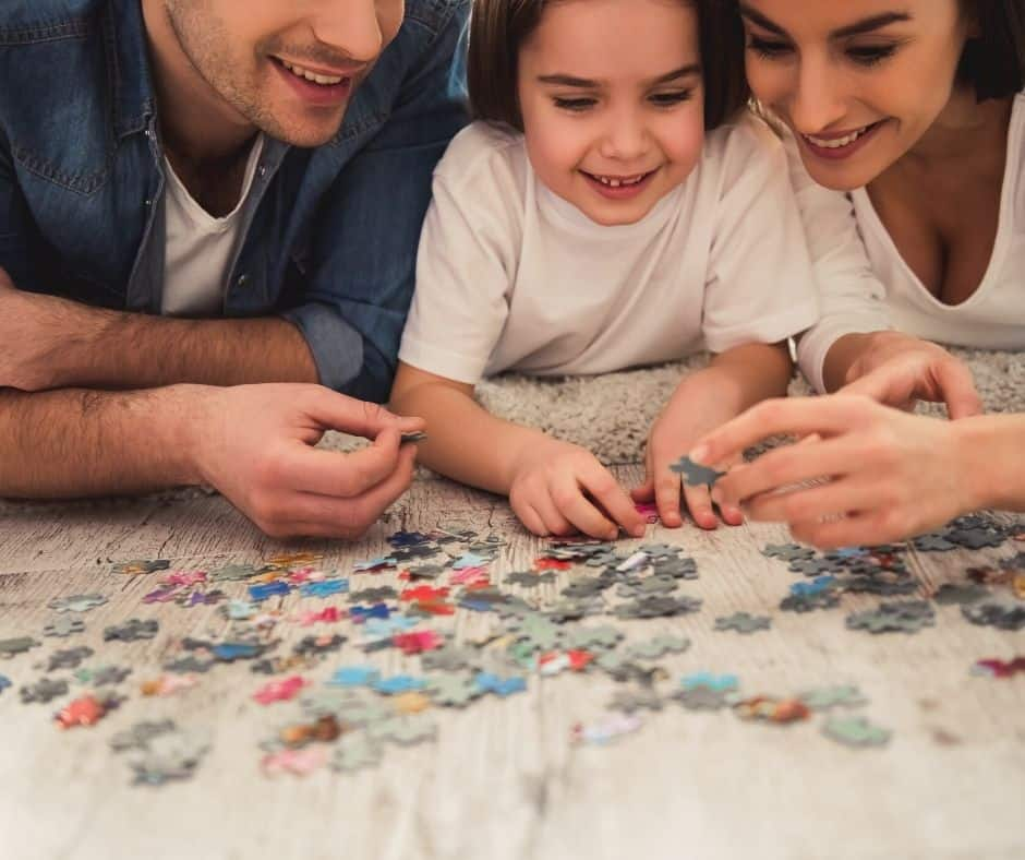 puzzles over vacation family tradition idea with three people working puzzle